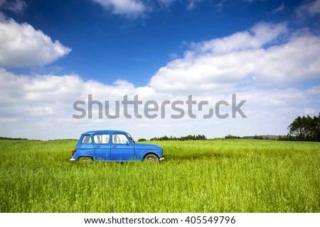 Beautiful old vintage car on a green meadow - stock photo
