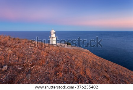 Beautiful old white lighthouse on the ocean coastline on the mountain at sunset. Summer seascape