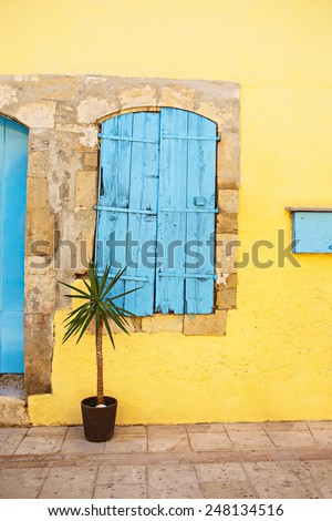 Beautiful old window decorated with plant. Blue window on a yellow wall. Mediterranean village style architecture.  - stock photo