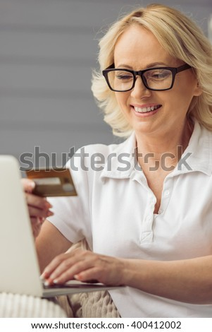 Beautiful old woman in casual clothes is holding a credit card, using a laptop and smiling while sitting in armchair at home