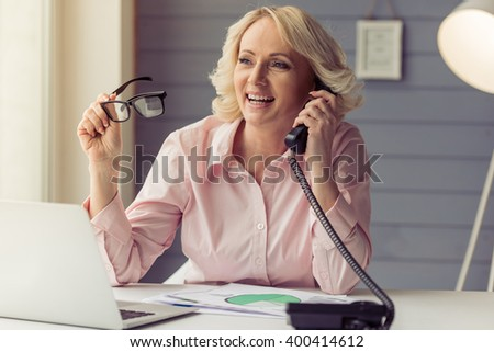 Beautiful old woman in classic shirt is talking on the phone, holding eyeglasses and smiling while working with a laptop at home - stock photo