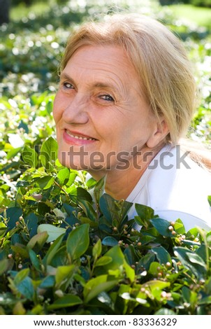 beautiful old woman lying on grass at park
