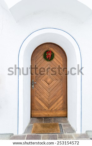 Beautiful old wooden door decorated by Christmas wreath - stock photo
