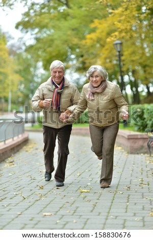 beautiful older couple walking in the park in early autumn