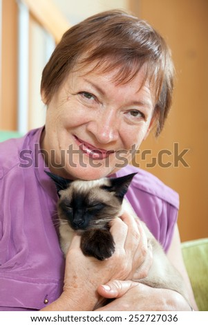 Beautiful older woman with  Siamese kitten in  arms.  - stock photo
