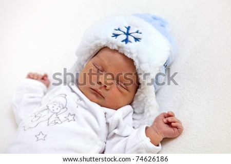 Beautiful one week old baby boy in winter hat asleep - stock photo