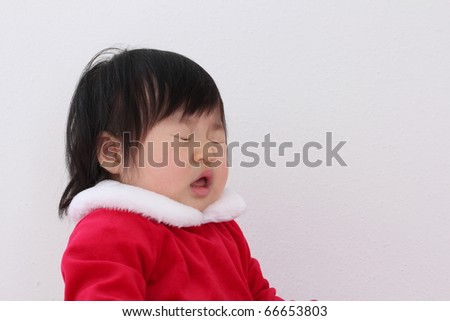 Beautiful One Year Baby Asian Toddler in Red and While Santa Suit Getting Ready to Sneeze while Celebrating Christmas Holiday with Good Cheer
