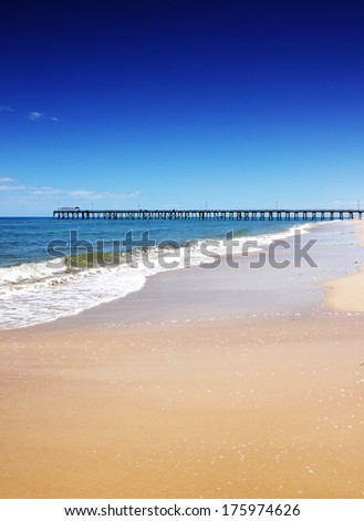 Beautiful open beach with blue skies and golden sands on sunny Summer day with Grange Jetty pier in background horizon. Taken at Henley Beach, South Australia. - stock photo