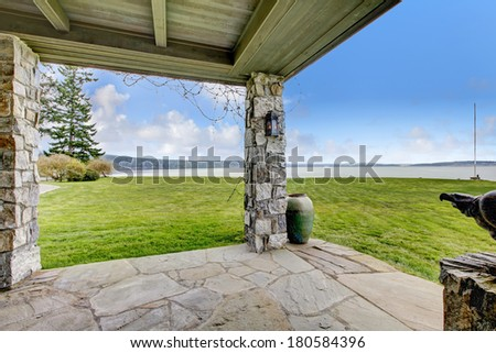 Beautiful open stone porch with columns. Porch overlooking picturesque landscape. - stock photo