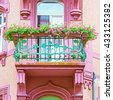 Beautiful openwork metal balcony with geranium flowers on a pink house, Heidelberg Germany - stock photo