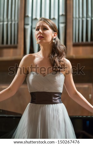 Beautiful opera singer sings emotionally in the concert hall - stock photo