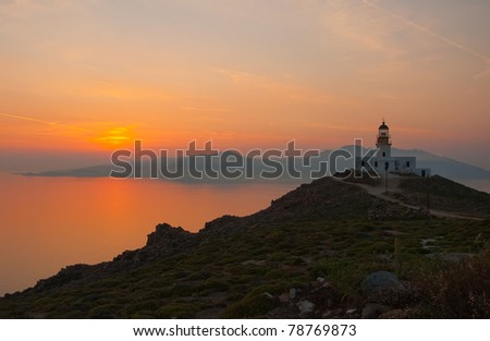 Beautiful orange sunset in the sea and the lighthouse on the island of Mykonos. Greece. - stock photo