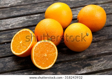 Beautiful Oranges Fruit Full and Sliced on old wooden table. rich with vitamins. background, texture. - stock photo