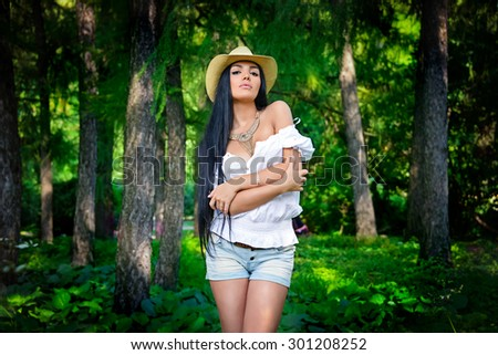 Beautiful Oriental girl in cowboy hat standing in a colorful fairy forest. - stock photo