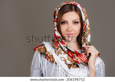 beautiful oriental look. portrait of a beautiful young woman with a scarf on her head. Russian beauty. Russian national traditional scarf on head.   - stock photo