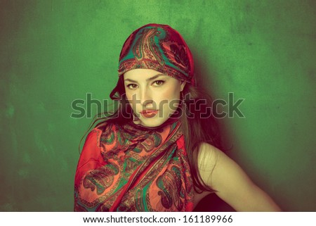 beautiful oriental look young woman with scarf on green background - stock photo