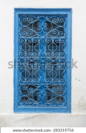 Beautiful ornamental blue windows on a white wall so typical for Tunisia, - stock photo