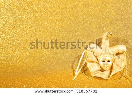 Beautiful ornate carnival venetian mask as christmas decor on golden glitter background - stock photo