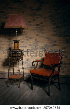 Beautiful ornate stand lantern standing near a leather armchair in empty room. Nice play of shadows on the wall. Copy space - stock photo