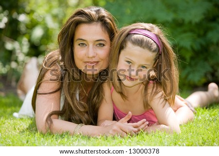 Beautiful pair of mother and daughter outside in the grass - stock photo