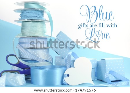 Beautiful pale aqua baby blue gift wrapping and ribbons on blue and white background with copy space for Fathers Day, Baby Boy shower or christening, or masculine birthday, wedding or shower present. - stock photo