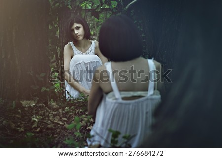 Beautiful pale woman in front of a mirror.  Surreal and dark - stock photo