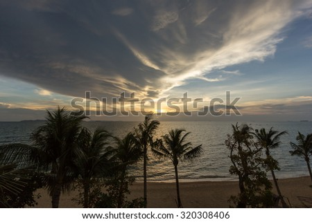 Beautiful Panorama Aerial View Exotic Sunset at Sea under Golden Sky Dramatic Cloud with Coconut and Palm silhouette foreground on the beach in Summer at Pattaya Beach, Thailand - stock photo