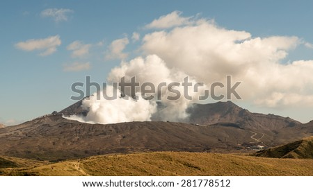 Beautiful Panorama Aerial View Smoke Gas Steam Crater of Mount Aso Volcano Caldera largest active Volcano in Japan Island eruption under Sunny Clear Blue Sky in Summer Daytime, Kumamoto, Kyushu - stock photo
