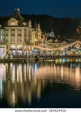 Beautiful Panorama Night view over old town city center skyline cityscape, Harbor, Christmas Light Decorated Krongasse Bridge and famous white Castle Gutsch on a hill from Lake Lucerne, Switzerland - stock photo