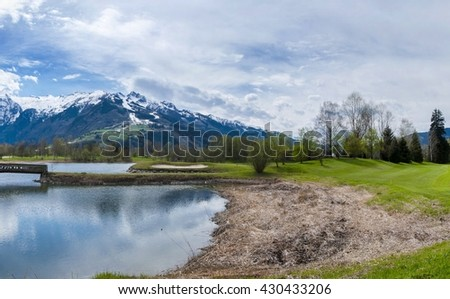 Beautiful panorama of golf resort with Alps mountains behind in Austria. Place for golf sport activity in summer with blue sky and clouds