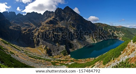 beautiful panorama of mountain peaks with the turquoise lake - stock photo