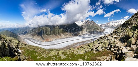 Beautiful panorama of the breathtaking Aletsch glacier as seen from the Bettmer alp in switzerland, on a sunny day with clouds in summer. - stock photo