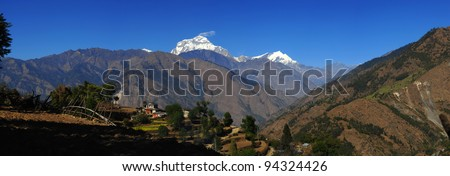 Beautiful panorama view of green field, local house and Himalayan mountains when see during Poonhill trekking way, Nepal - stock photo