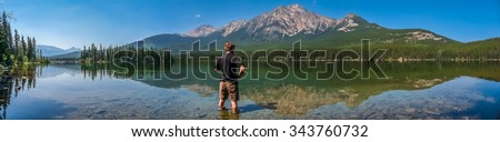 Beautiful panoramic view of lonely man standing in Pyramid Lake with great mountain landscape in the background, Jasper National Park, Alberta, Canada - stock photo