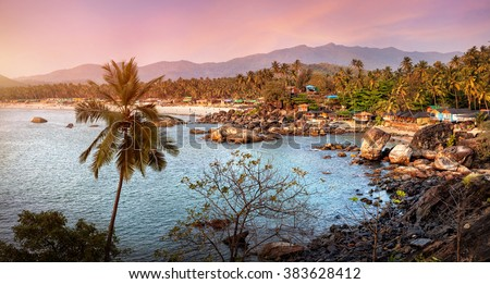 Beautiful panoramic view of tropical sunset beach with bungalow and coconut palm trees at Palolem in Goa, India  - stock photo