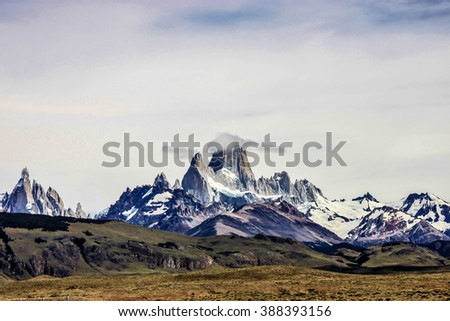 Beautiful panoramic view on the high mountains with snow in El Chalten, Argentina. Cloud is covering the top of one rock. No sun, brown landscape. - stock photo