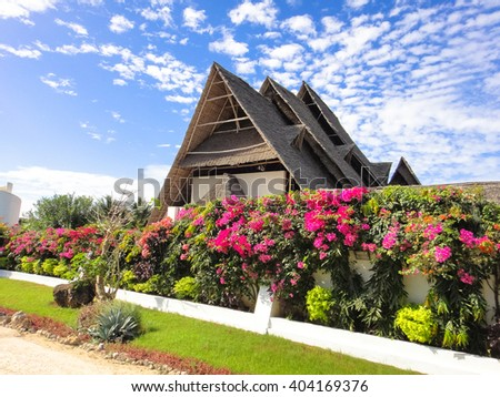 Beautiful paradise beach and african house with blue sky and clouds on a blue background