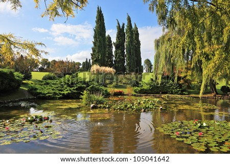 Beautiful park Sigurta in northern Italy. Weeping willows and cypresses in a quiet pond - stock photo
