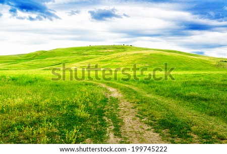 Beautiful path through green hills with white cloudscape. - stock photo