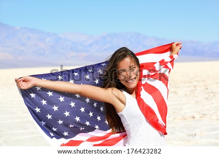Beautiful patriotic vivacious young woman with the American flag held in her outstretched hands standing in the summer sunshine in front of an expanse of white sand and distant mountains - stock photo