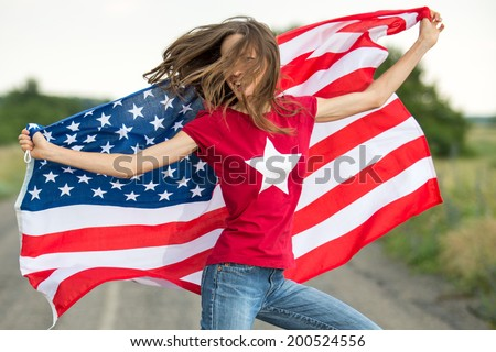 Beautiful patriotic  young woman with the American flag held in her outstretched hands running along the road with flying hair - stock photo
