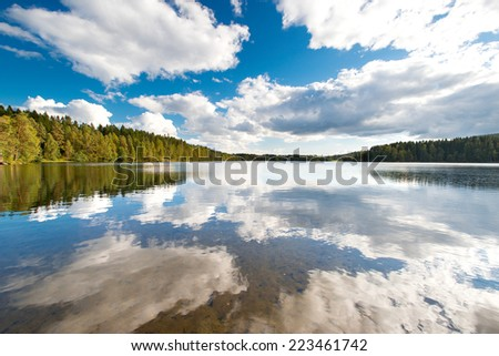 Beautiful peaceful lake surrounded by trees - stock photo