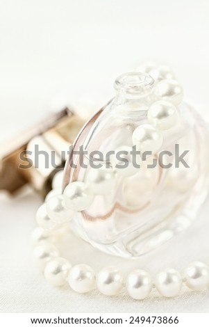 Beautiful pearl necklace draped over a delicate bottle of perfume. Extreme shallow depth of field with selective focus. - stock photo