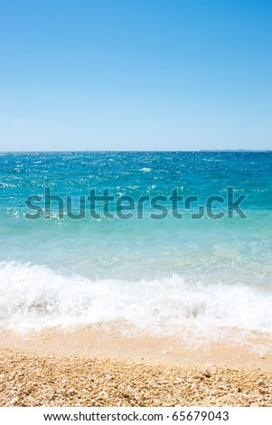 beautiful pebbles beach with waves and blue sky - stock photo