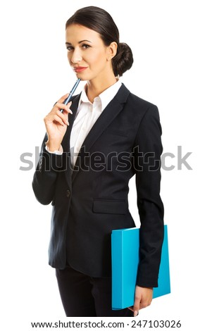 Beautiful pensive businesswoman holding a pen. - stock photo