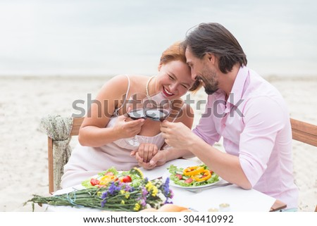 Beautiful people having rest in the restaurant. Man and woman having lunch with red wine, people laughing, hugging and kissing.