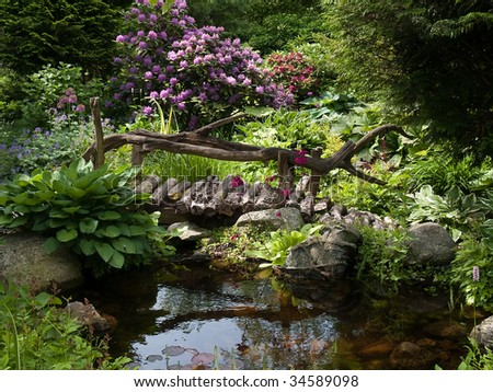 Beautiful perfect backyard landscaped garden with wooden bridge - stock photo