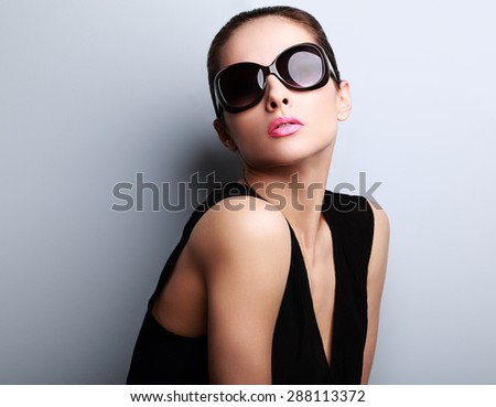 Beautiful perfect young woman posing in fashion sunglasses on blue background with empty copy space