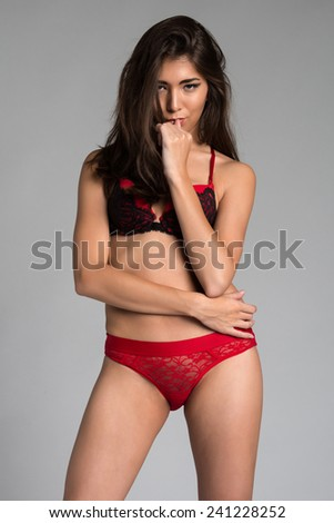 Beautiful petite Eurasian woman in red and black lingerie - stock photo