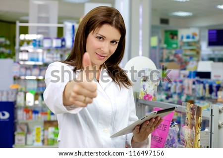 Beautiful pharmacist working in pharmacy with ipad thumb up - stock photo